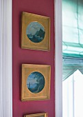 Vertical row of framed landscapes in gilt mounts on claret wall