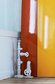 Vintage water pipes with stop cocks in front of lacquered panels in bright orange and yellow
