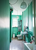 View through open door into narrow bathroom in period apartment painted mint green with white pendant lamps
