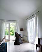 Buffalo hunting trophy on wooden floor in corner of living room with airy, white curtains on French windows