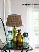 Vintage swing-top bottles and table lamp with checked lampshade on side table
