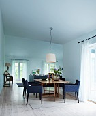Chairs upholstered in blue around wooden table in open-plan interior with minimalist atmosphere