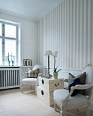 Stack of pale, vintage trunks flanked by Rococo-style armchairs against striped wallpaper in elegant interior
