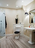 Traditional bathroom; pedestal toilet with cistern against wooden panel in corner, pedestal sink and modern glass shower cubicle