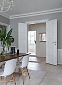 Essplatz mit Schalenstühlen im Klassiker Stil gegenüber offene Flügeltür mit Blick in Küche einer Altbauwohnung