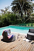 Cool off in the pool - dark brown rattan outdoor easy chairs on wooden deck next to pool in tropical garden