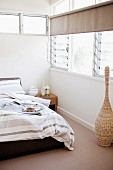 Bed with striped bed linen in shades of grey and brown in corner of bedroom with louvre windows and transom window