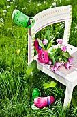 Tulips and garden clogs on child's chair in tall grass