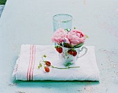 Peonies and wild strawberries in teacup