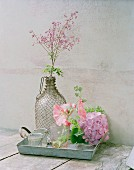 Chinese meadow rue in demijohn with wire mesh cover next to hydrangea and hollyhock flowers