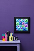 Hand-crafted, 3D-effect artwork made from blue, green and purple origami squares of different sizes on violet wall; matching ornaments on desk