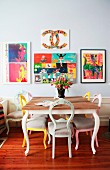 Dining area with antique chairs painted in various colours and colourful pictures on light grey wall in period apartment