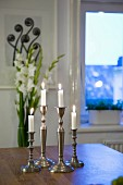 Lit candles in silver candlesticks on table