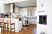 Wooden bar stools at breakfast bar integrated into kitchen counter below stainless steel extractor hood in open-plan, white country-house kitchen