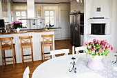 Bouquet of tulips on white dining table, counter and bar stools in front of white, open-plan country-house kitchen