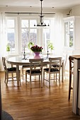 Oval dining table and white wooden chairs below wrought iron chandelier in front of window