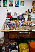 Paints and paintbrushes on vintage work table below postcards of artworks pinned to wall of painter's studio