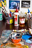 Paint remnants in bowl and paintbrushes on work table in painter's studio