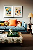 Blue sofa, colourful scatter cushions and tea set on tray on ottoman in living room