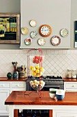 Decorative plates and wall clock on extractor hood above gas cooker in country-house kitchen with fruit and vegetables in 3-tier wire basket