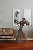 Geige spielende Frauenfigur aus Drahtgeflecht vor moderner Kunst an der Wand, daneben Rokoko Polsterbank