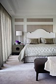 Double bed with curved, white-painted wooden headboard against wood-panelled wall with white frames in elegant bedroom