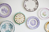 Collection of plates with rustic motifs and retro clock on wall