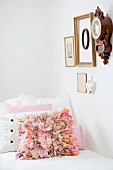 Scatter cushion with pink ruffles on couch below antique clock and various framed picture on wall