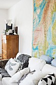 Various scatter cushions on white sofa in front of map of the world on wall and rustic wooden cabinet in background