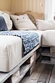 Nahaufnahme einer selbstgemachten Sitzbank aus Holzpaletten und hellen Sitzpolstern mit Flickenteppich und Kissen