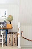 Offener Dachraum mit weisser Holzverkleidung, Ausschnitt eines Schreibtisches und Vintage Koffer neben Treppenhaus Wand