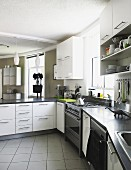 L-shaped counter in modern kitchen with white cabinets and tiled floor