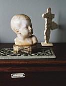 Stone bust of child on trivet