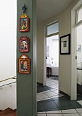 Colourful panels hanging in vertical row on wall in hallway with tiled floor and curved wall; view into neighbouring rooms through open doors