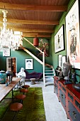 Simple wooden table and chairs, antique Oriental sideboard, green walls and wood-beamed ceiling in eclectic interior
