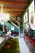 Schlichte Holztischgarnitur gegenüber antikem, asiatischem Sideboard in eklektizistischem Wohnraum mit grünen Wänden und Holzbalkendecke