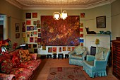 Sofa in vintage floral pattern and pale blue armchairs in artistic interior; large painting surrounded by many small paintings on wall