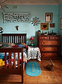 Wooden bed with slatted headboard and foot next to chest of drawers against turquoise-painted wall in artistic interior