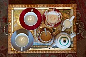 Top view of antique tray holding contemporary and traditional teacups and saucers