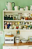 Crockery and collection of vintage enamel jugs on retro kitchen shelves on pale green wall