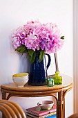 Pink flowers in blue jug on console table made of bent bamboo