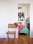 Schlichter Klappstuhl aus Bambus im Vorraum an Wand, seitlich offene Tür und Blick auf Bett mit Palmenmotiv an Wand