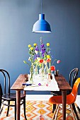Bottles of spring flowers on simple wooden table with white runner, Thonet chairs and classic shell chair against blue-painted wall