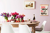 White, retro-style shell chairs around glass vases of flowers and red fruits on antique wooden table against pastel pink wall