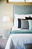 Modern bedroom with bed, scatter cushions and lamp on bedside table