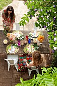 Two women sitting at set garden table below flowering shrub in summery garden party atmosphere