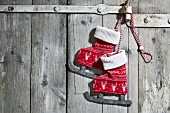 Pair of textile ice skate decorations hanging on wooden door