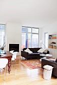 Eleganter offener Wohnraum mit Parkettboden und dunkelbrauner Ledercouchgarnitur
