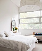 Bright, white bedroom with wide ribbon window and tall mirror leaning against wall on top of bedside cabinet