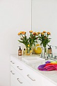 White, washstand cabinet, mirrored wall and vase of yellow flowers in designer ambiance